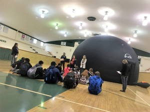 students sitting on gym floor in front of large blue inflatable dome