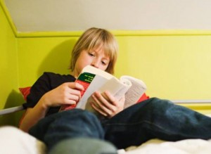 blond boy reading in bed